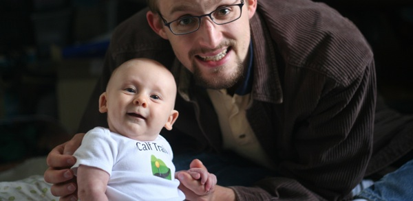 Software developer holding smiling son, who is proudly wearing a company logo